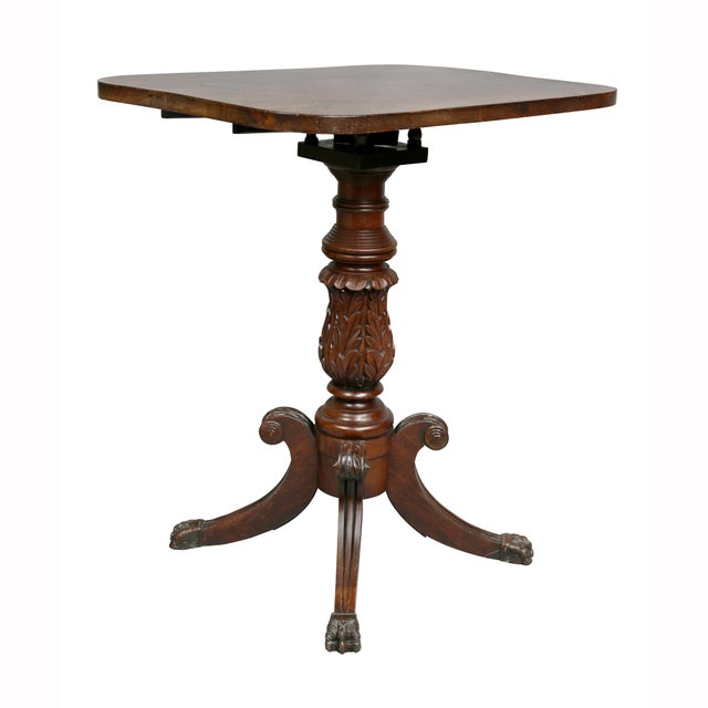 Antique table with rectangular tilt-top over a turned and carved support, with four saber legs ending on carved paw feet....