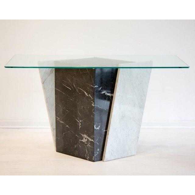 A unique marble console table featuring nero marquina black marble diamond shaped base with two white marble slabs...