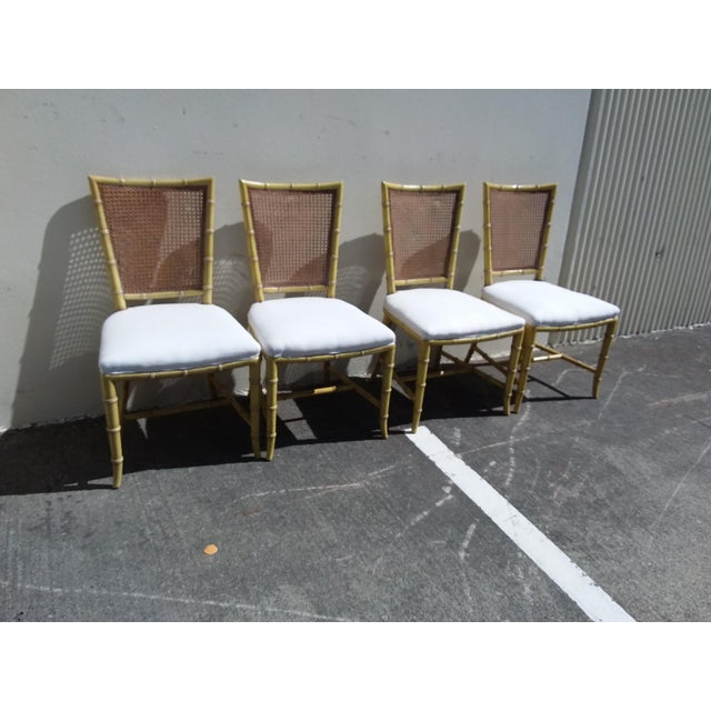 Set of Four bright yellow mid century modern faux bamboo side chairs with woven cane backs. The painted finish is worn...