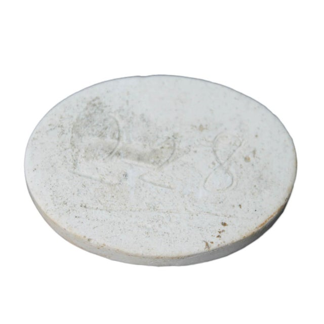 A faint plaster cameo of possibly a man and two horses.