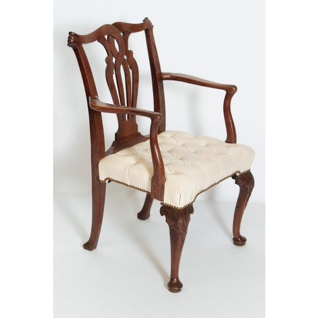 A early George III Chippendale armchair with tufted off white leather seat. Serpentine crest rail ending with scrolled...