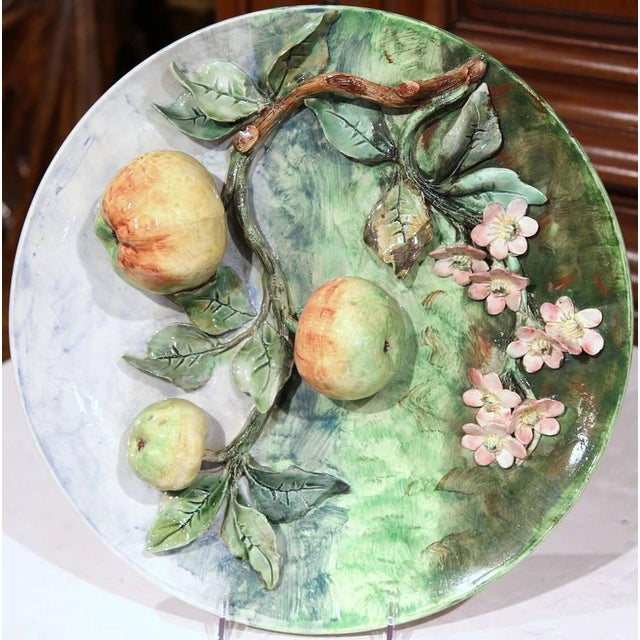 This colorful, antique Majolica plate was sculpted in France, circa 1880. The round, hand-painted platter has pink flowers...