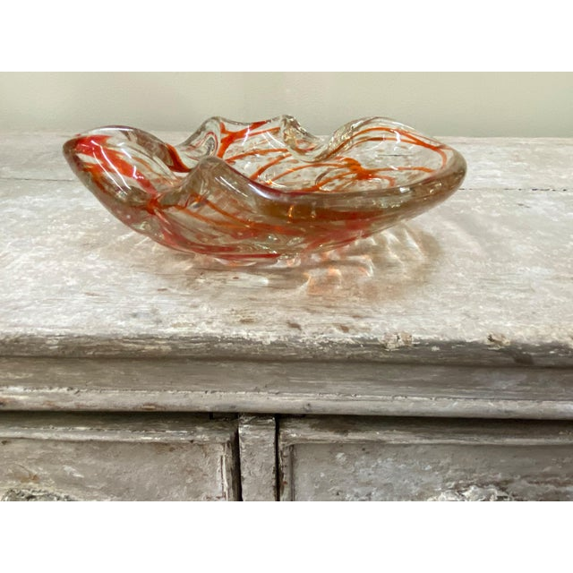 A lovely shaped clear mid century Murano glass bowl with orange ribbon like streaks and metallic gold flecks throughout....