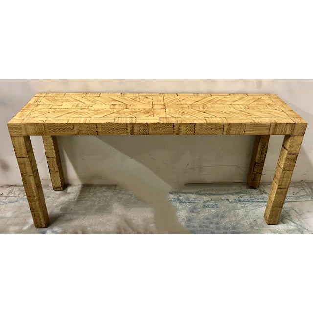 1970s wood and laminate console table in the style of James Mont. It has a marbleized finish on it's parson's style frame.
