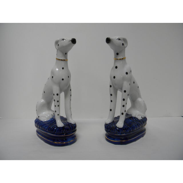 Pair of figurative ceramic Dalmatians in the style of Staffordshire bookends. Each of these elegant figures is standing...