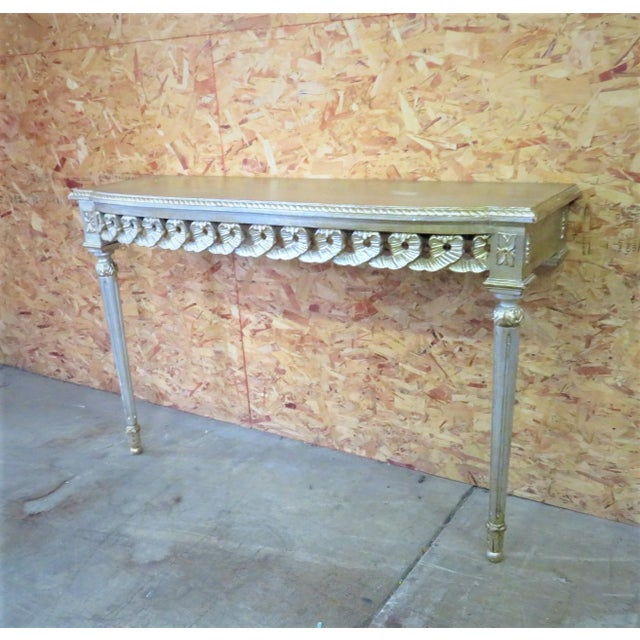 Silver gilt Florentine console table with ribbon carved skirt.