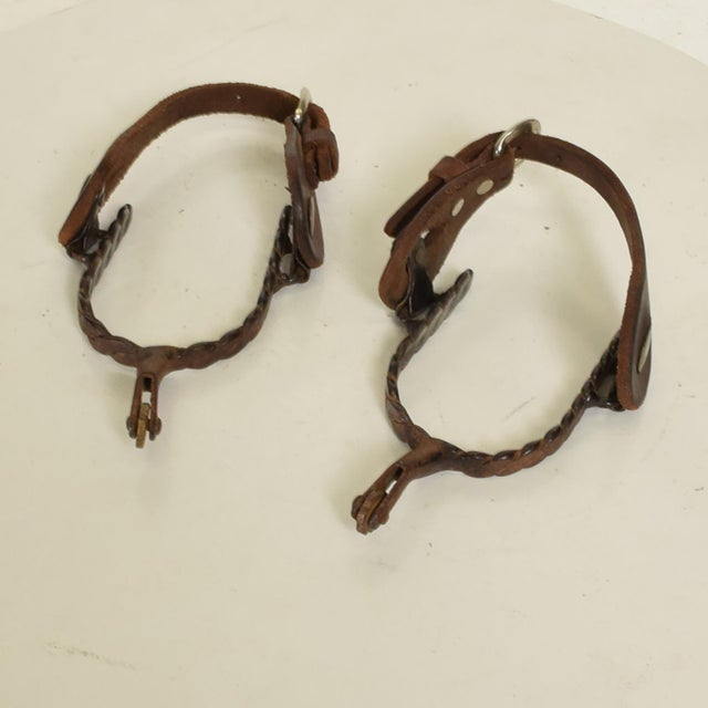 For your consideration, Antique Forged Iron Western Spurs with Leather & Brass Accent. Unmarked, no information on the...