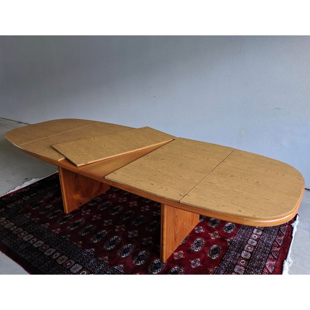 Danish Modern 1970s teak oval dining table with two removable leaves and custom protective pads. Table would benefit from...