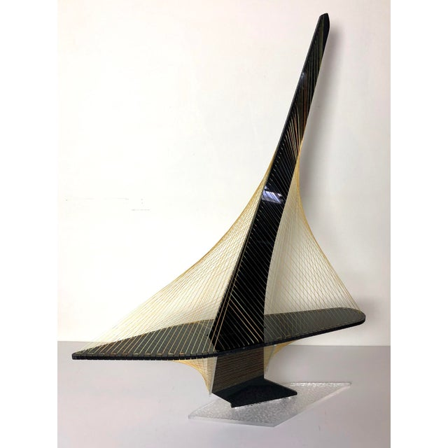 A tall sleek vintage string art sailboat. Featuring a black lucite body and a clear lucite textured base with gold and...