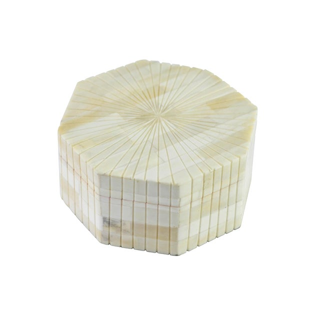 An octagonal bone box with a starburst-like pattern radiating from the center of the lid.