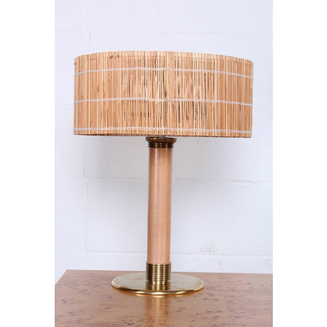 An elegant brass and wood lamp with original reeded shade. Designed by Paavo Tynell for Taito.