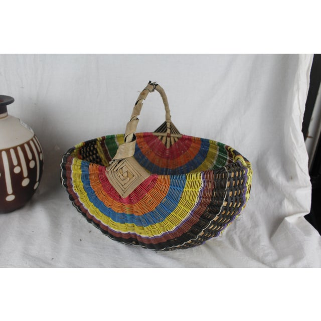 Handwoven Zulu telephone wire basket with rainbow pattern and tan handle. Made in the mid 20th century.