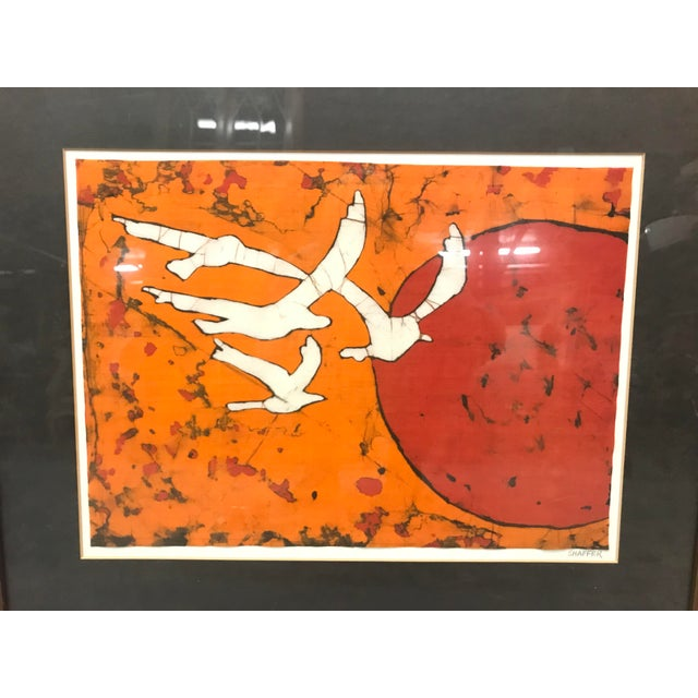 Mid-century modern abstract lithograph of birds and a sunset in orange and red. In a wooden frame with black matte.