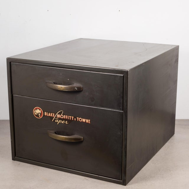 ABOUT An army green industrial factory two drawer metal cabinet with original label, brass pulls and bottom segmented...