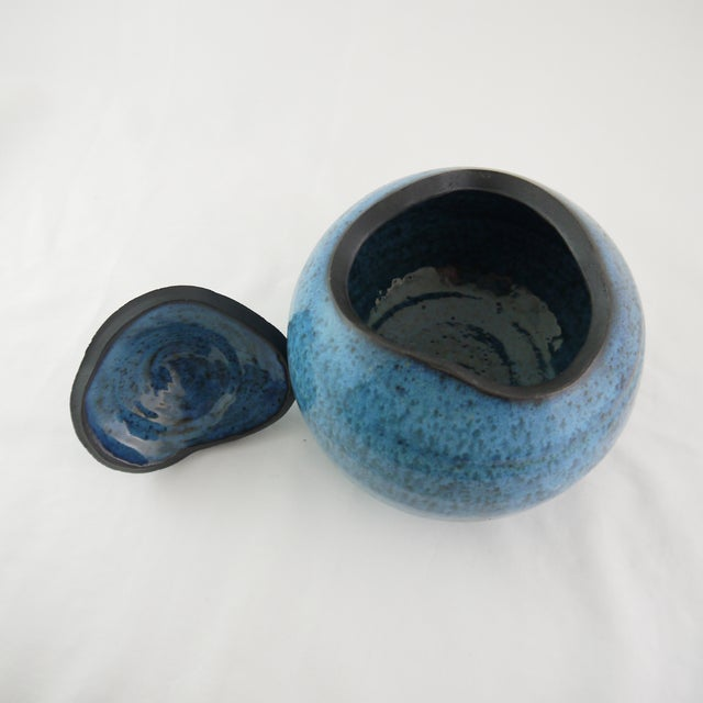 "Sky blue ceramic vase or jar with lid with dotted detailing on top. Unique and one-of-a-kind. Approximately 6"" wide by 6""..."