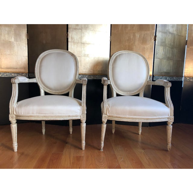 Pair of early 19th century Louis XVI style fauteuil armchairs with hand-carved frames featuring oval backs with partially...