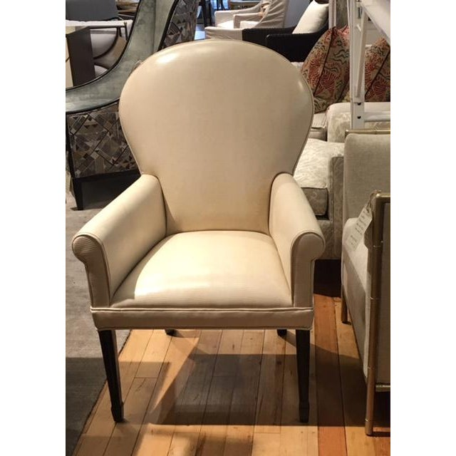 Leathercraft's Ophelia chair is covered in Iquana/Ivory leather. The finish on the legs is a dark walnut. The chair has...