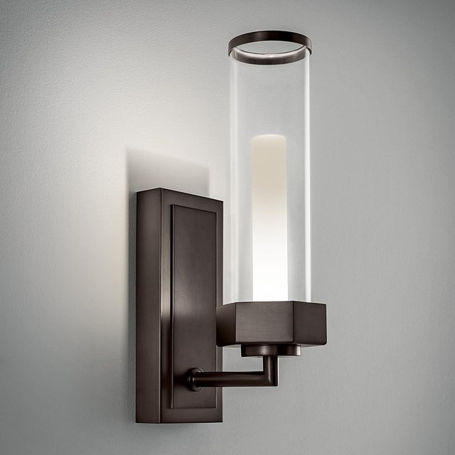 A black bronze bathroom wall light with an integral LED light source. The light shines upwards into a heavily frosted...