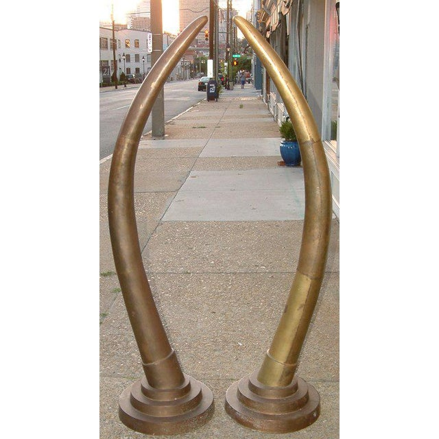 Circa 1970. A rare pair of fabricated yellow bronze tusks in the art deco style purchased from a Palm Beach, Florida...