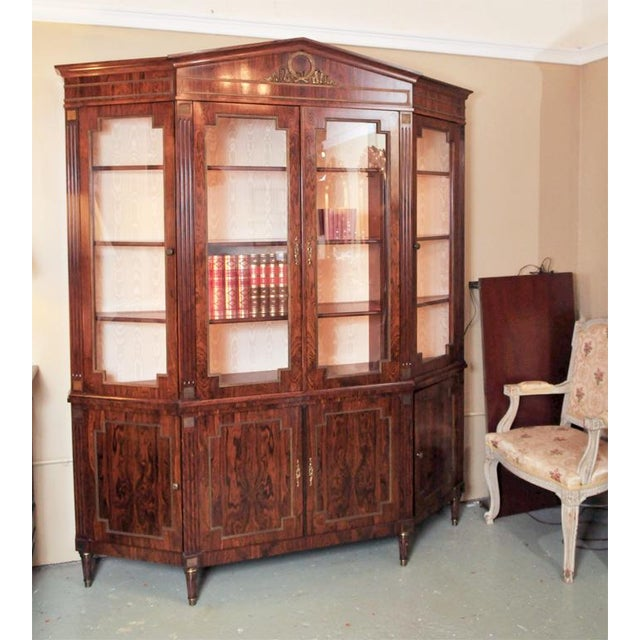 The seller says: Finest rosewood and ormolu mounted bookcase/breakfront with a beautifully carved ribbon-form medallion...