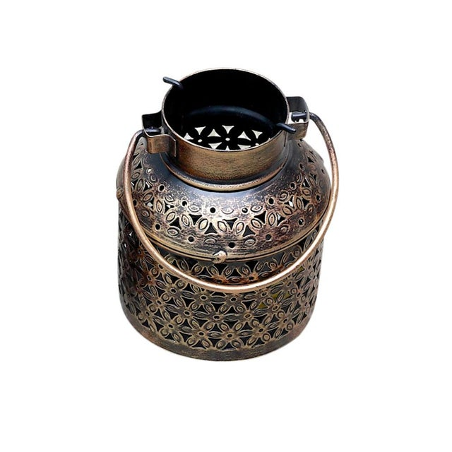 This Filigree metal candle holder features a striking laser cut design to feature a floral and geometric pierced design...
