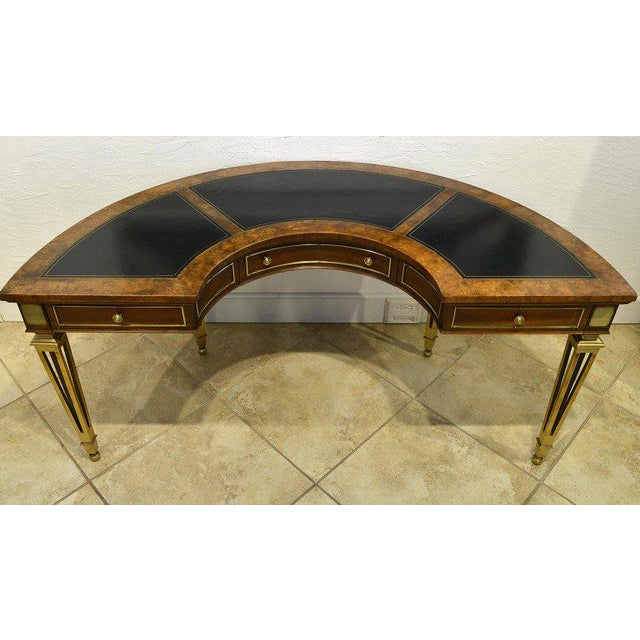 This magnificent Mastercraft semi-circular desk features a top inlaid with three panels of gilt tooled leather above three...
