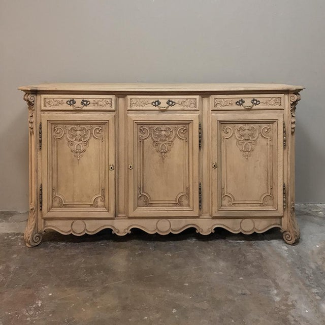 19th Century Country French Regence Stripped Oak Buffet features the unique blend of Rococo and Baroque styling that was...