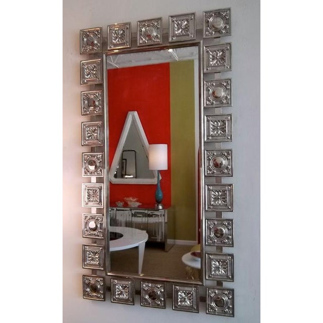 This unusual mid century modern 1950's mirror features alternate squares of two different impressed designs. A fleur de...