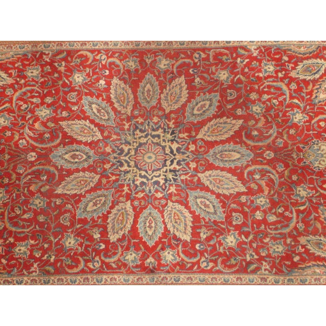 Nothing adds a timeless elegance to a space like a fine Persian Sarouk area rug. This handmade piece features rich,...