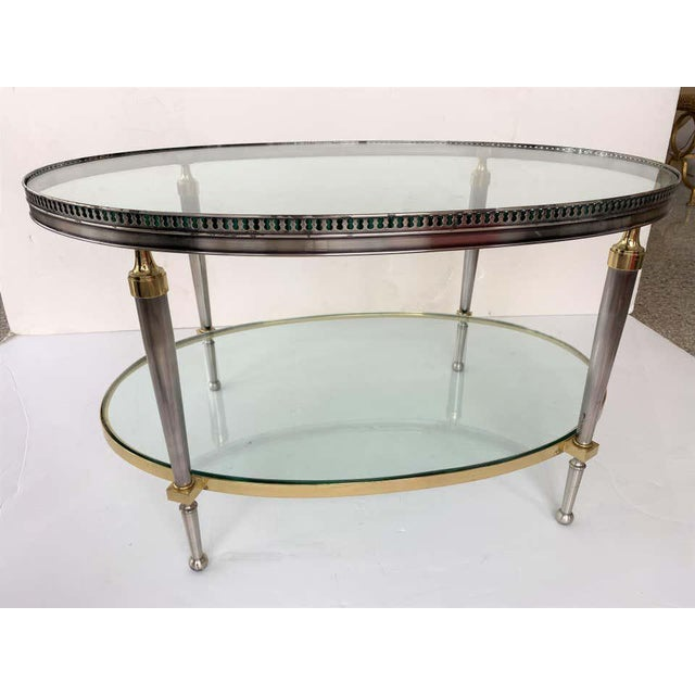This stylish campaign style, oval-form, two-tiered cocktail table dates to the 1970s and was designed and fabricated by...