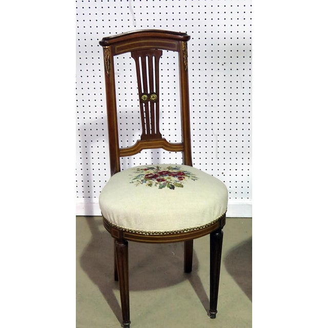 Pair of Directoire style slipper chairs with needle point upholstery, gilt highlights, and nail head trim.