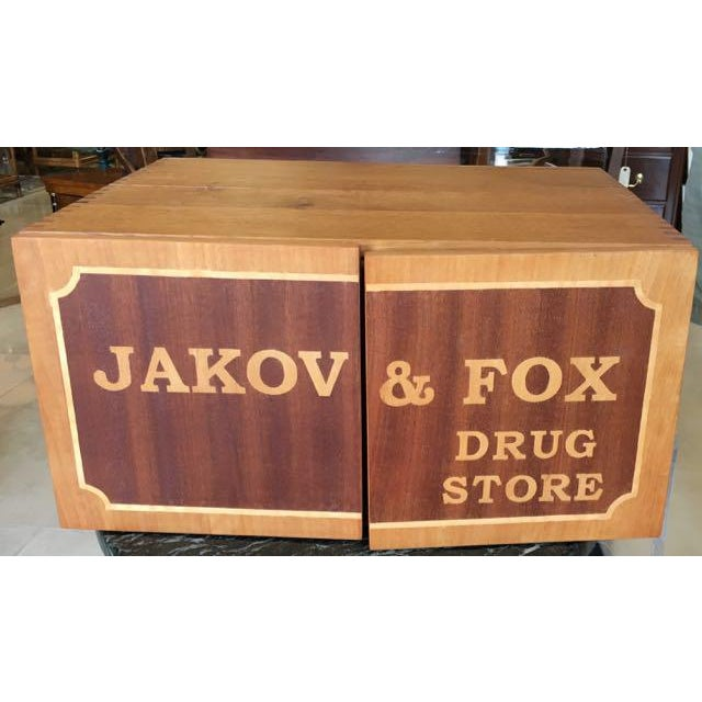 Hand made wooden model of an old fashioned general store. To visit the Jakov & Fox Drug Store, open the flaps to see the...