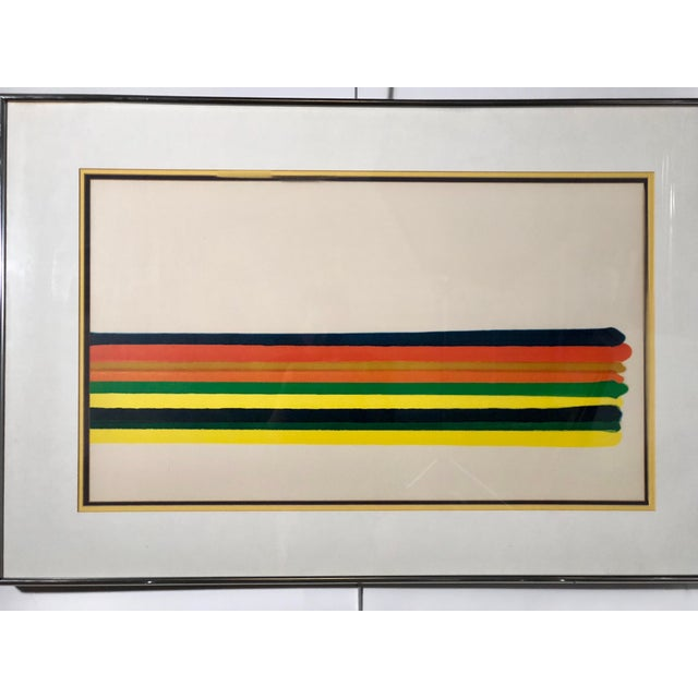 Large print of a horizontal stripe in primary colors of red, green, orange, and blue. It is held under plexiglass by blue,...