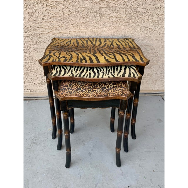 A unique Set of nesting tables with faux bamboo legs and animal print resin tops. Each table shows a different large cat...