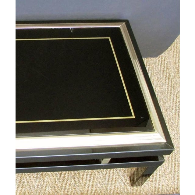 A stylish French 1970s black enameled metal rectangular coffee or cocktail table with brass detailing and églomisé glass...