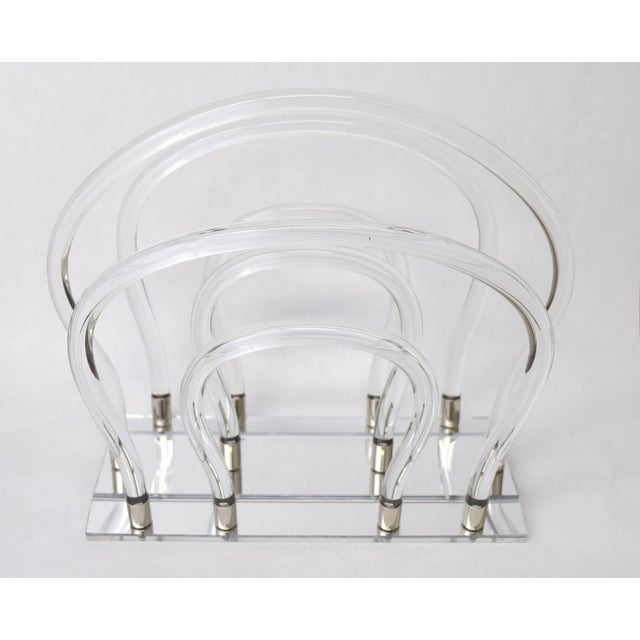 Iconic magazine rack by Dorothy Thorpe executed in chrome tipped bent Lucite tubes on mirrored base.