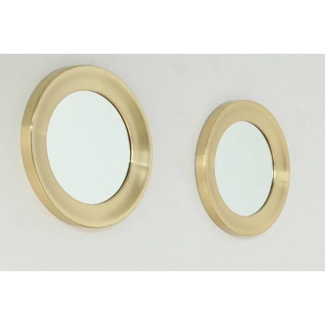 A pair of round, brass mirrors by Glasmäster, Markaryd, Sweden. The mirrors are marked by Glasmäster and are in a great...