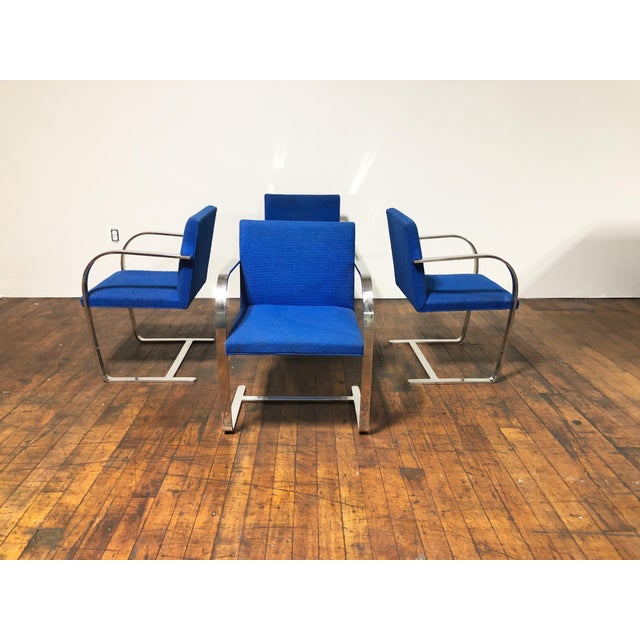 Set of four original Ludwig Mies Van der Rohe solid polished steel flat bar Brno chairs in original cobalt blue upholstery...