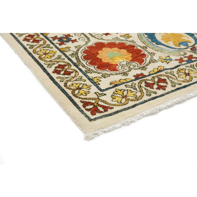 Made in Pakistan. Inspired by embroidered Suzani textiles from Uzbekistan, this rug features floral motifs in modern...