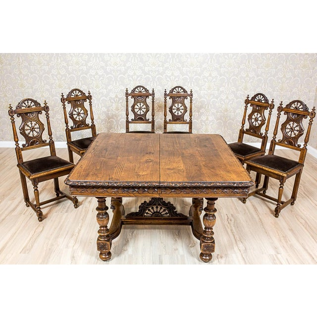 Presented table and six chairs are made in solid oaken wood. The table is in the form of a square on four turned legs,...