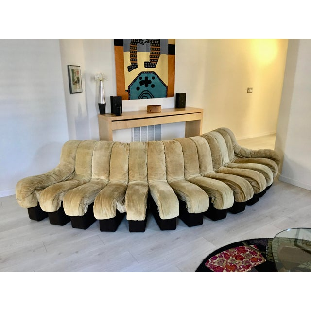 Sofa consists of 19 sections, original tan suede upholstery and brown felt base and back. 17 are seating sections and 2...