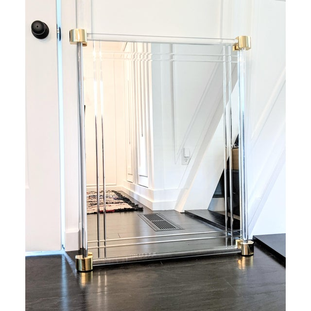 Elegant, lucite framed wall mirror with brass corner details. This striking vintage mirror features an inset bevel detail....