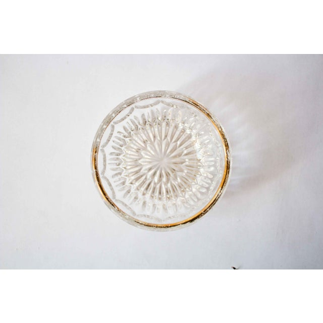 Sophisticated and subtle carved glass bowl with gold leaf accent on the rim. A beautiful way to store odd and ends in the...
