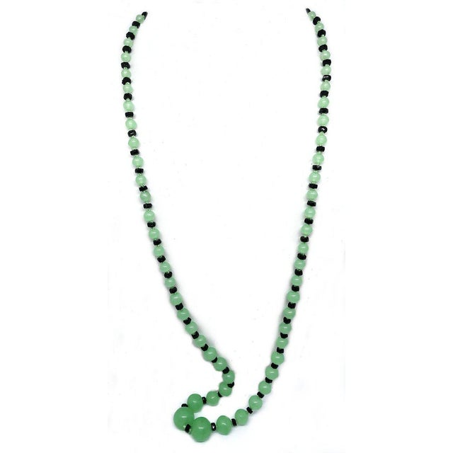 c1920 bright green glass bead hand knotted necklace in graduated sizes with black glass spacers. The beads are 13mm to 5mm...