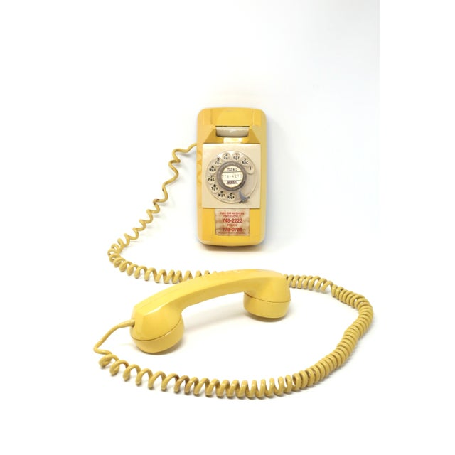 A vintage, yellow 1976 Starlite / American Electric wall phone with rotary dial and extra long cord. Good vintage...