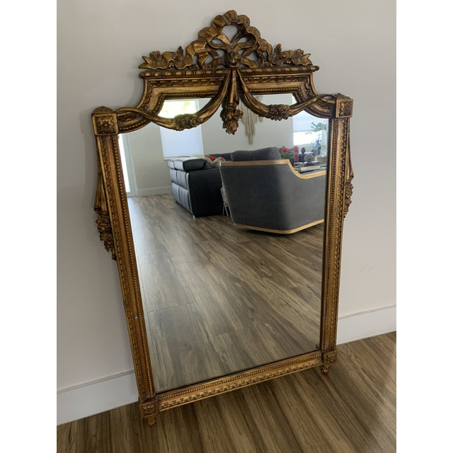 Italian Rococo style mirror. Gilt carved ribbon draped, wood.