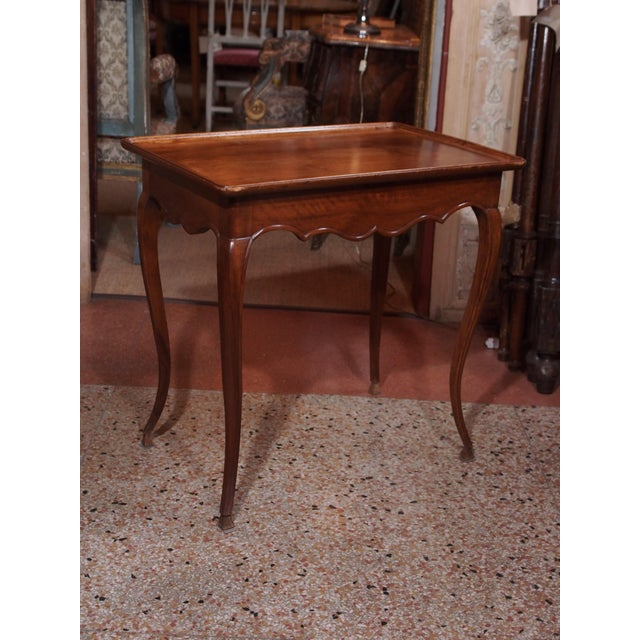 Late 19th century walnut side table. The plateau has an upward lip. Scalloped apron on four sides. Delicate cabriole legs...