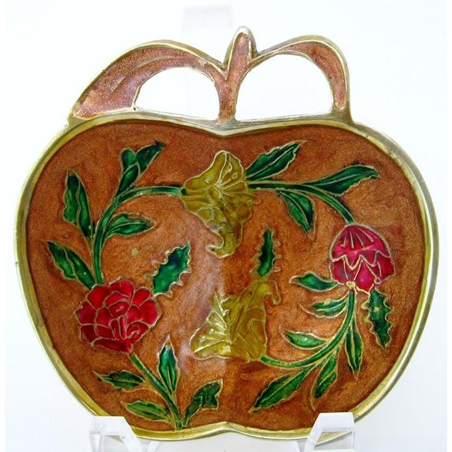 Apple-shaped brass trinket dish with floral motif-enameled center. Purchased in Germany, no maker's mark. There is light...