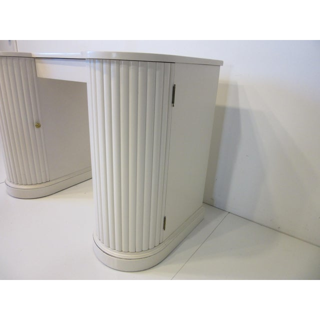A creamy white well constructed double column vanity or writing desk with upper middle drawer, brass pull to each column...