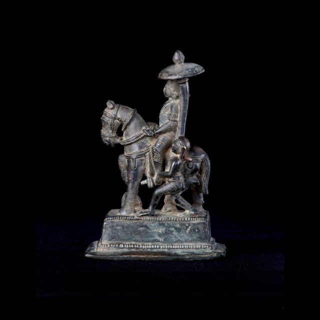This well-made bronze piece is an indian representation of an aristocrat or deity, as evidenced by the parasol being held...